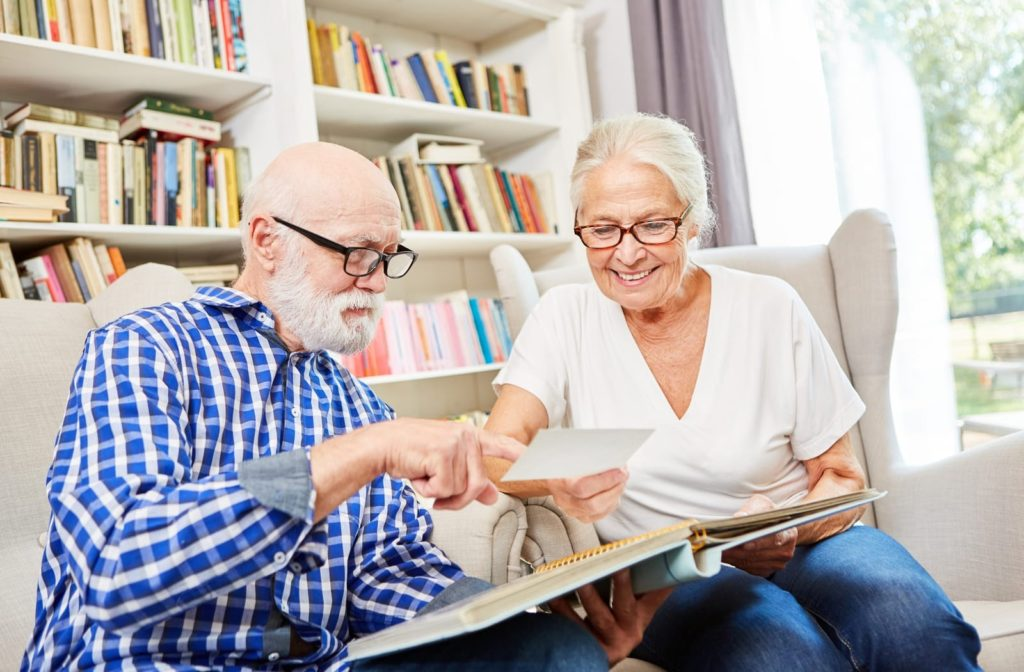A senior couple look through a photo album together as part of memory therapy