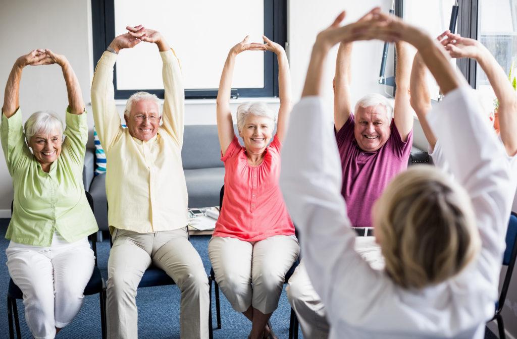 Happy seniors stretching and exercising in senior community.