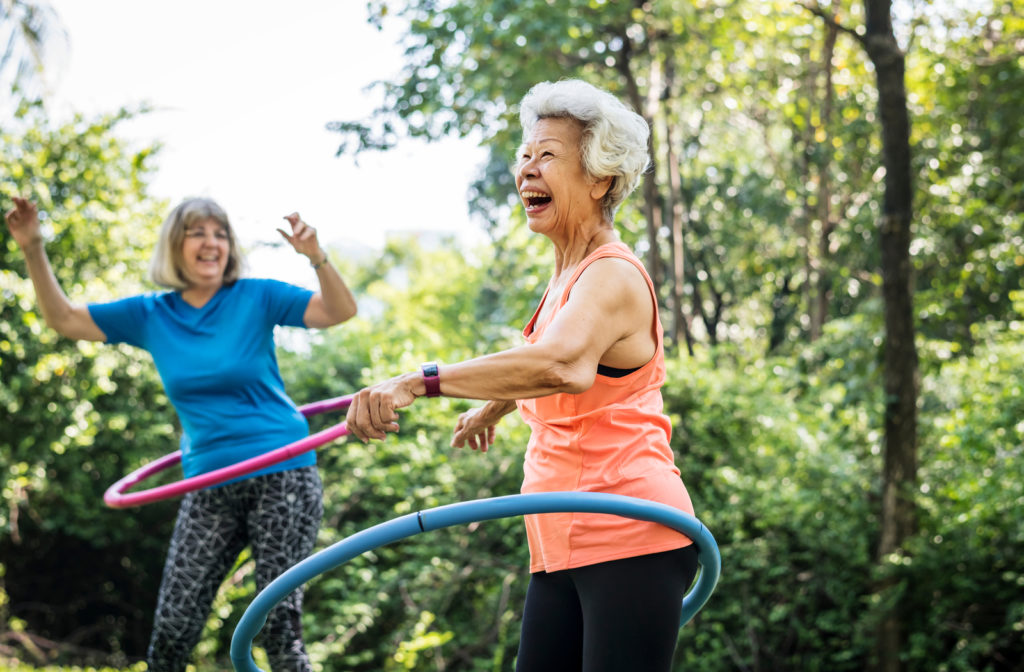 Two happy senior women exercising outside using hula hoops